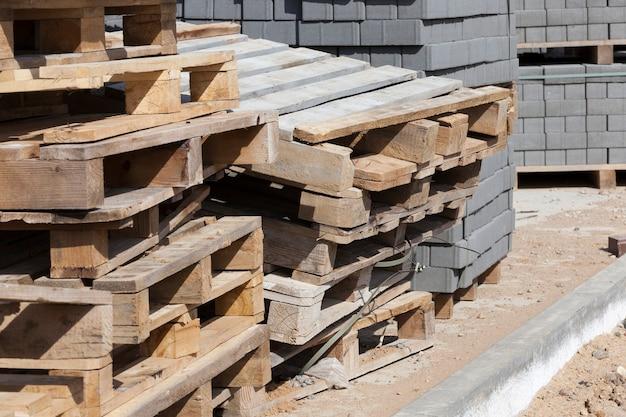 Paletes de madeira vazios e novos ladrilhos de construção para colocar caminhos e estradas