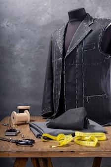 Paletó em manequim alfaiate masculino e acessórios de costura, conceito criativo de ateliê de roupas