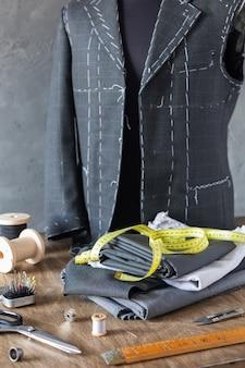 Paletó em manequim alfaiate masculino e ferramentas de costura, conceito criativo de ateliê de roupas