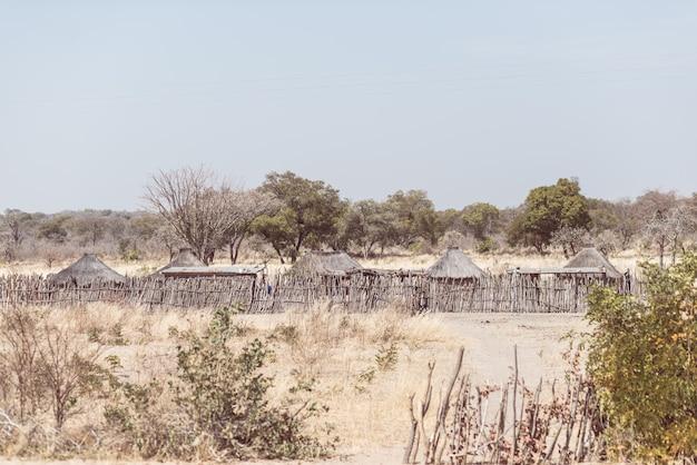 Palha da lama e cabana de madeira com o telhado cobrido com sapê no arbusto. vila local na faixa de caprivi rural, a região mais populosa da namíbia, áfrica.