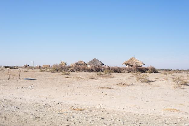 Palha de lama e cabana de madeira com telhado de colmo no mato. namíbia, áfrica.