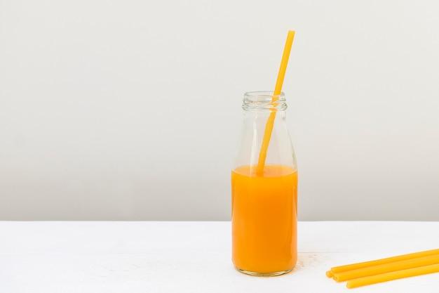 Palha de macarrão em uma garrafa de vidro com conceito de desperdício zero de suco de pêssego
