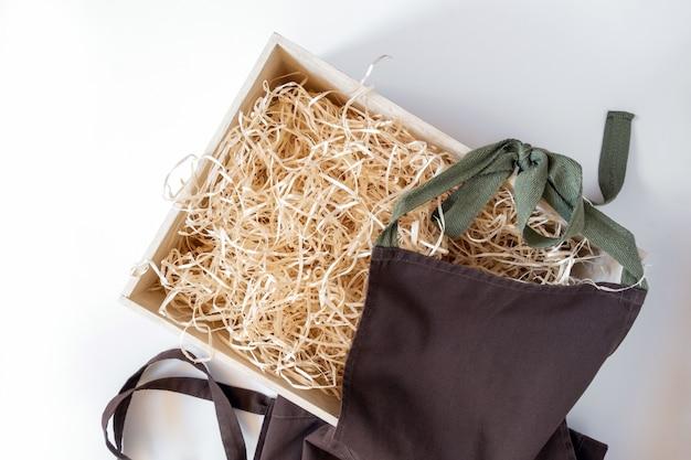 Palha em caixa de armazenamento para vinho e avental marrom no fundo branco, serviço de entrega.