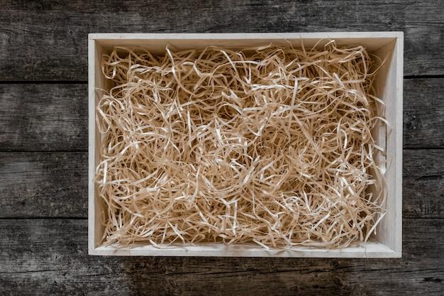 Palha em caixa de armazenamento para vinho no fundo preto de madeira, serviço de entrega.