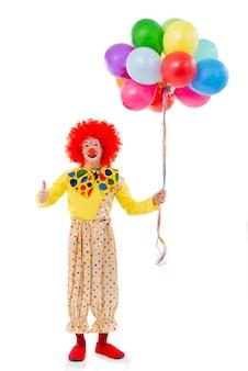 Palhaço brincalhão engraçado na peruca vermelha que mostra o sinal aprovado.