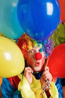 Palhaço com um monte de balões de ar coloridos.