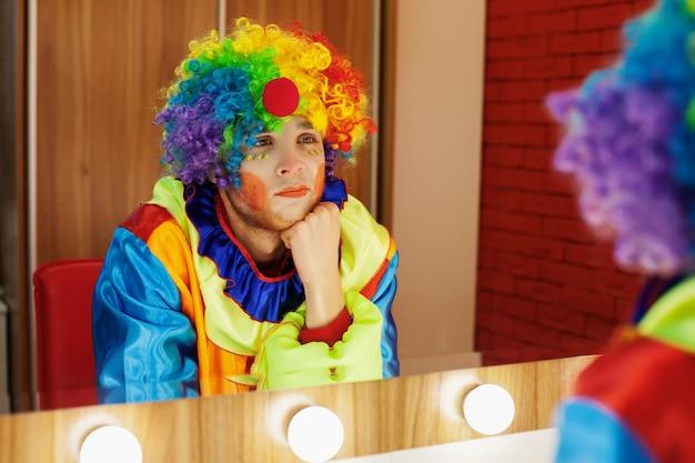 Palhaço de circo se olha no espelho da sala de maquiagem.