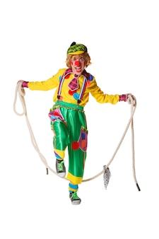 Palhaço engraçado salta sobre uma corda de pular isolada no branco