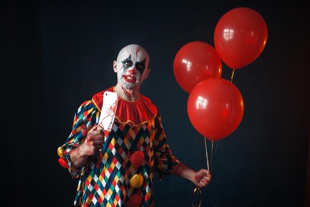 Palhaço feio e sangrento com cutelo segura balão de ar, horror. homem maquiado em fantasia de carnaval, maluco maníaco