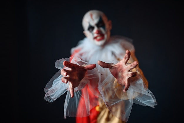 Palhaço louco tentando alcançar a vítima com as mãos, vista frontal. homem maquiado em fantasia de carnaval, maluco maníaco