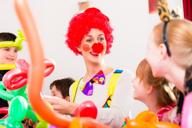 Palhaço na festa de aniversário infantil entretendo as crianças