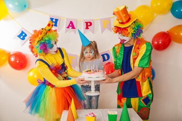 Palhaços emocionais alegres em um feriado com crianças explodem o bolo