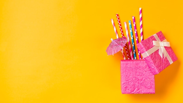 Palhas bebendo coloridas com pequeno guarda-chuva na caixa-de-rosa sobre fundo amarelo