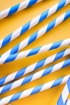 Palhas coloridas, reutilizáveis, listradas para beber suco ou coquetel em fundo amarelo.