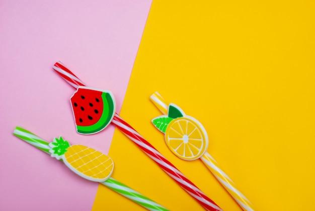 Palhas em forma de melancia, limão e abacaxi em um fundo rosa e amarelo