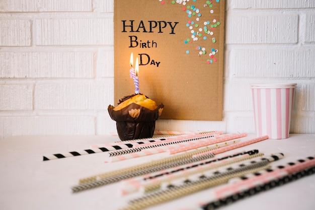 Palhas perto de muffin e saudação de aniversário