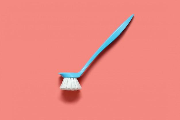 Pálida escova azul para lavar pratos deitado no coral vivo.