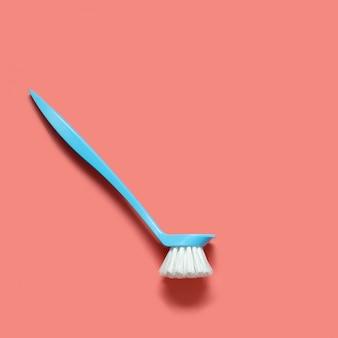 Pálida escova azul para lavar pratos deitado no fundo de coral vivo