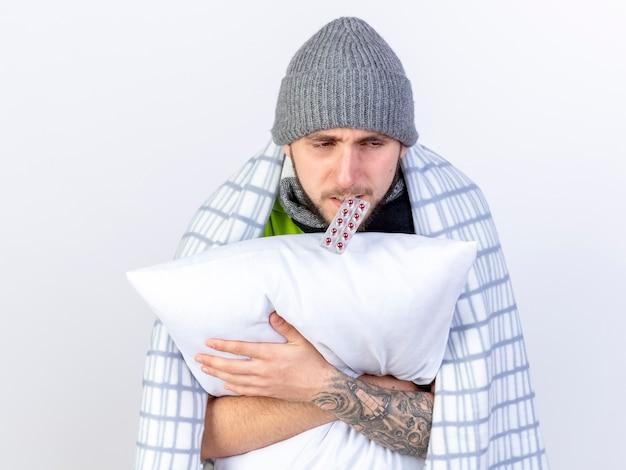 Pálido, jovem, caucasiano, doente, usando um chapéu de inverno embrulhado em manta segura um pacote de cápsulas médicas com dentes e uma almofada de abraços isolada no fundo branco com espaço de cópia