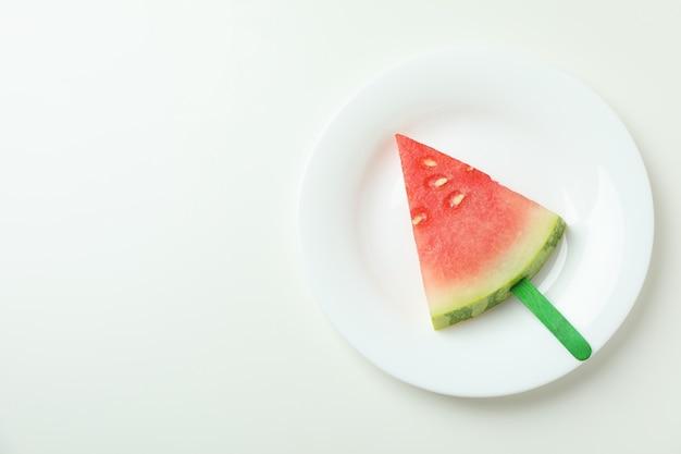 Palito de gelo com fatia de melancia no prato fundo branco