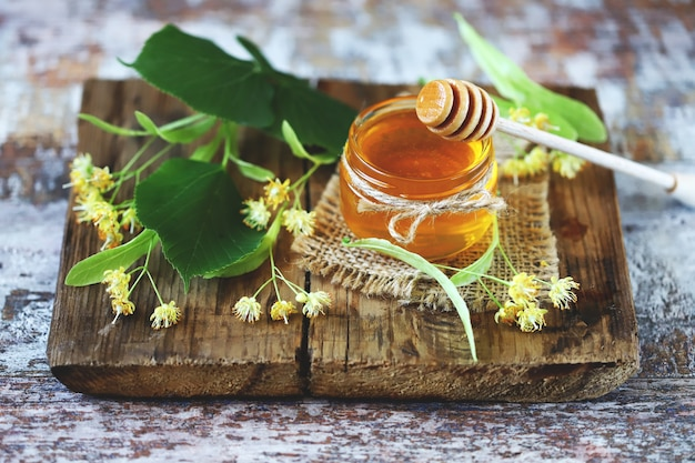 Palito de mel, frasco de mel de tília, flores de tília.