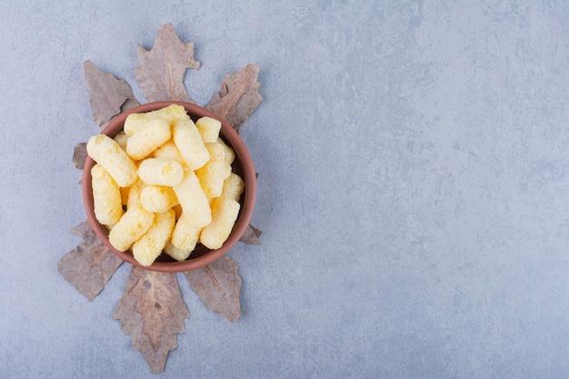 Palito de milho doce em uma tigela na folha na superfície azul