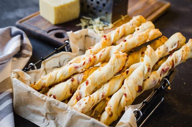Palito de queijo. palitos de pão com queijo no fundo escuro. conceito para lanche ou festa