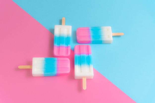 Palito de sorvete de frutas, picolé, gelo pop ou freezer pop em fundo pastel azul e rosa
