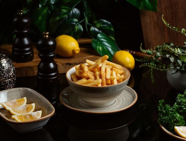 Palitos de batata finamente assados, servidos com fatias de limão