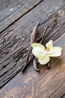 Palitos de baunilha secos e orquídea de baunilha na mesa de madeira. fechar-se.