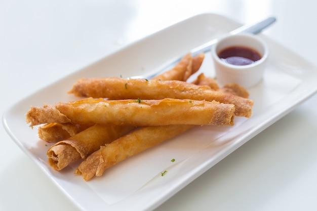 Palitos de camarão rolinho primavera frito servidos em um prato branco com molho.