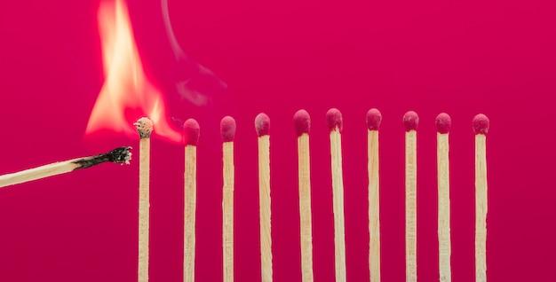Palitos de fósforo em chamas ateando fogo em seus vizinhos