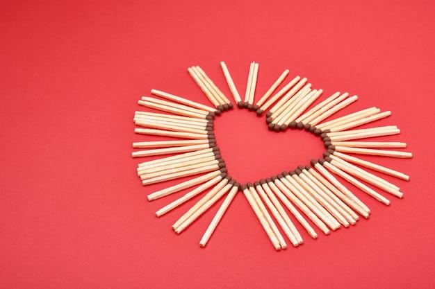 Palitos de fósforo em forma de coração em vermelho