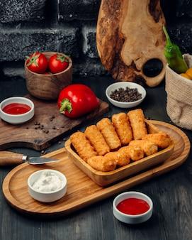 Palitos de frango frito em uma placa de madeira com maionese e molho de tomate.