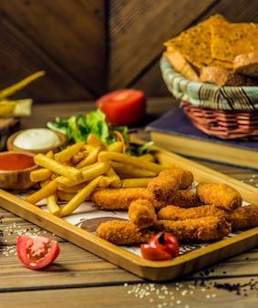 Palitos de frango servidos com batata frita, maionese e ketchup