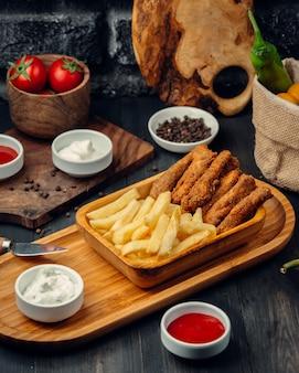 Palitos de frango servidos com batatas fritas maionese e ketchup