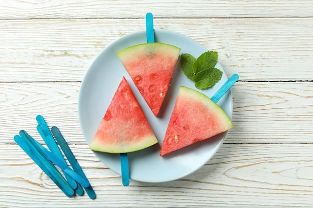 Palitos de gelo com fatias de melancia no prato na mesa de madeira branca