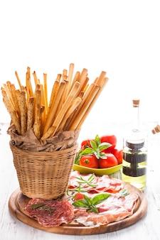 Palitos de grissini e antepasto de carne - aperitivo italiano