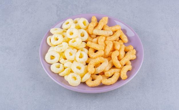 Palitos de milho e anéis de milho em um prato, no mármore.