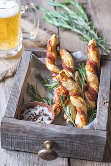 Palitos de pão embrulhados em bacon com caneca de cerveja