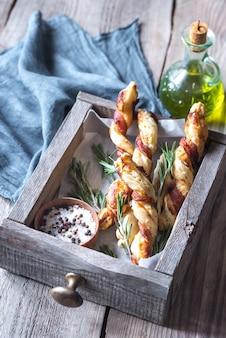 Palitos de pão embrulhados em bacon na bandeja de madeira