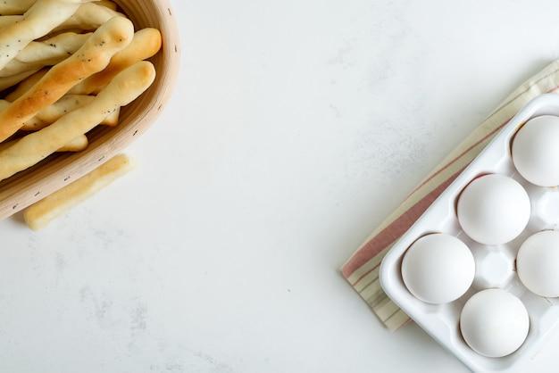 Palitos de pão italiano tradicional com papoula em uma cesta e bandeja de ovos orgânicos