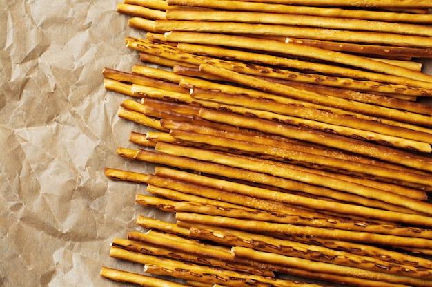 Palitos de pão salgado ou pretzel salgado e crocante longo em papel pergaminho em pedra cinza velha ou mesa de concreto. vista do topo.