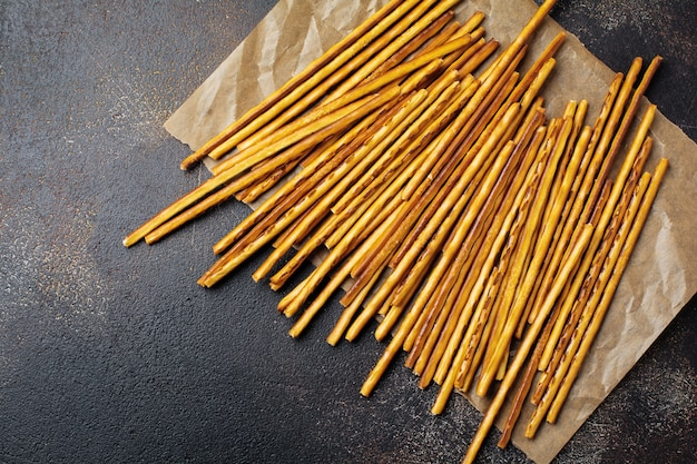 Palitos de pão salgado ou pretzel salgado e crocante longo em papel pergaminho em pedra marrom velha ou mesa de concreto. vista do topo.