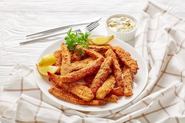Palitos de peixe à milanesa e assados, filé de peixe servido em um prato branco sobre uma mesa de madeira com molho tártaro e rodelas de limão, vista panorâmica de cima Foto Premium