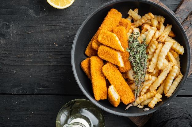 Palitos de peixe frito com batatas fritas. dedos de peixe. peixe com batatas fritas britânico, conjunto de batata frita, na frigideira, na mesa de madeira preta, vista de cima plana lay