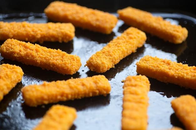 Palitos de peixe no fundo palitos de peixe frito em uma assadeira culinária como um aperitivo e comida