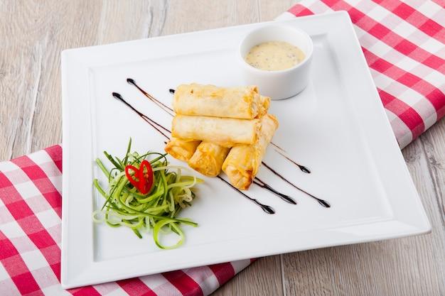 Palitos de queijo com molho de queijo de pepino em um prato branco