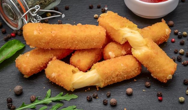 Palitos de queijo crocante com molho em um fundo de pedra preta