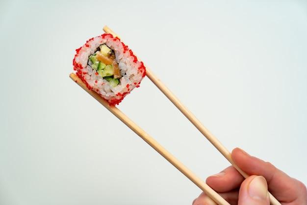 Palitos de sushi de madeira mantêm o rolo com caviar vermelho, peixe, arroz e abacate em um fundo branco. peça comida com entrega online. culinária japonesa.